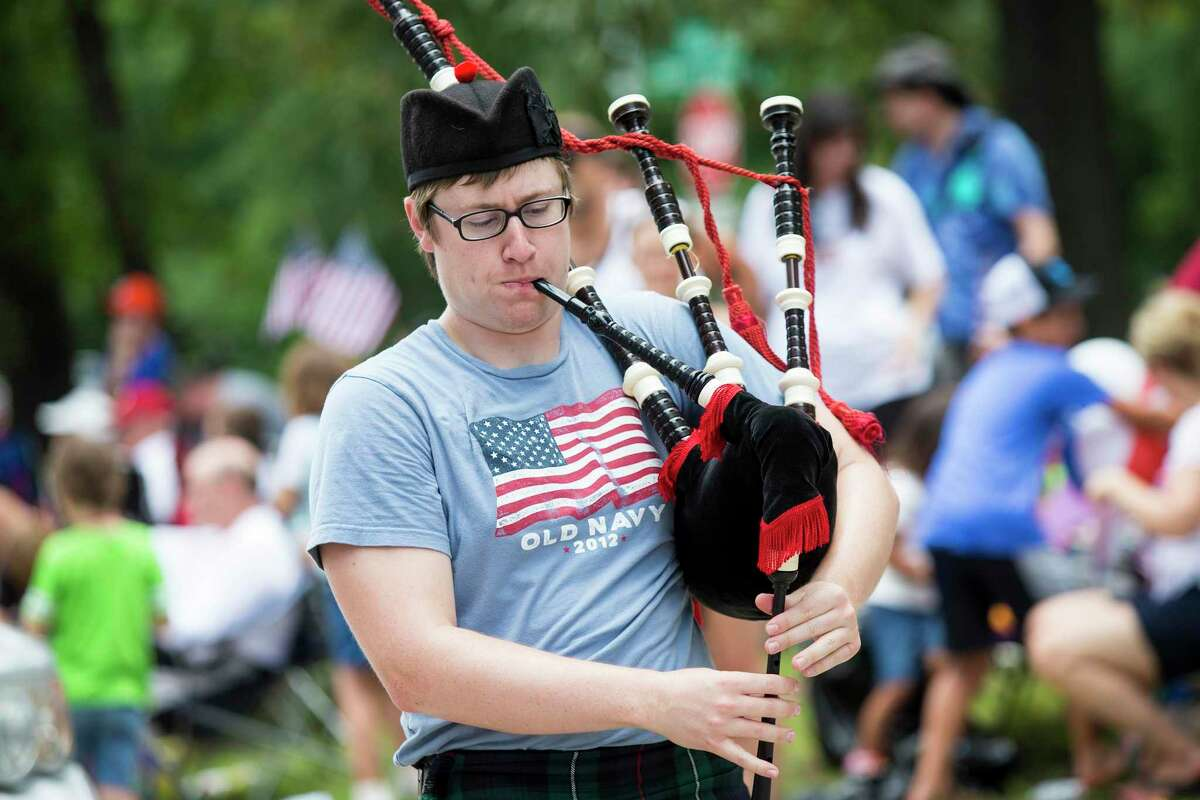Joe Stratton plays the bagpipes while leading the Kingwood Bible Churches float during the Kingwood Civic Club's 4th of July parade July 4, 2014, in Kingwood. Staff photo by Andrew Buckley