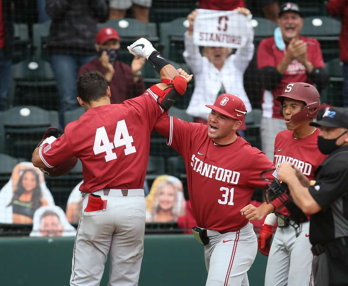 Stanford's Christian Robinson, left, celebrates his 12 inning home run against Stanford.