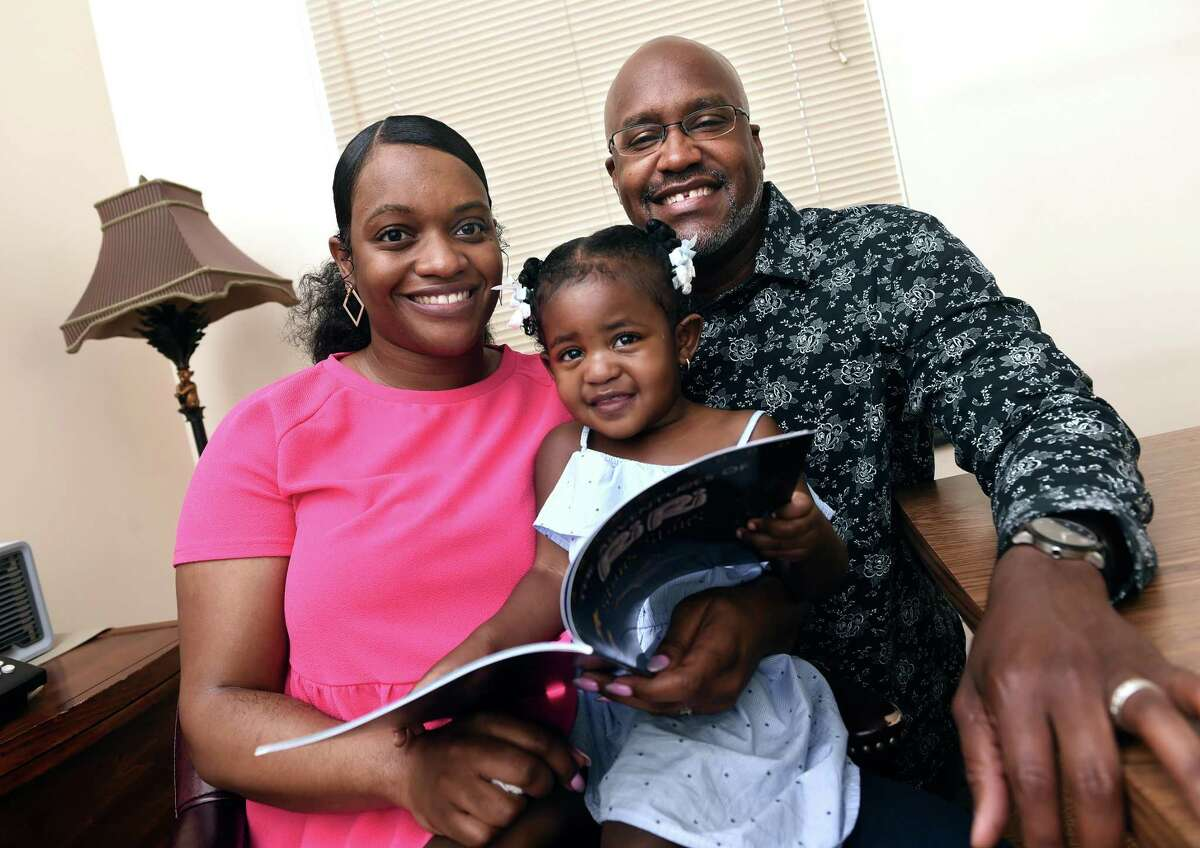 Darius Good, right, with his wife, Chazaree, and one-year-old daughter Riley, looking through