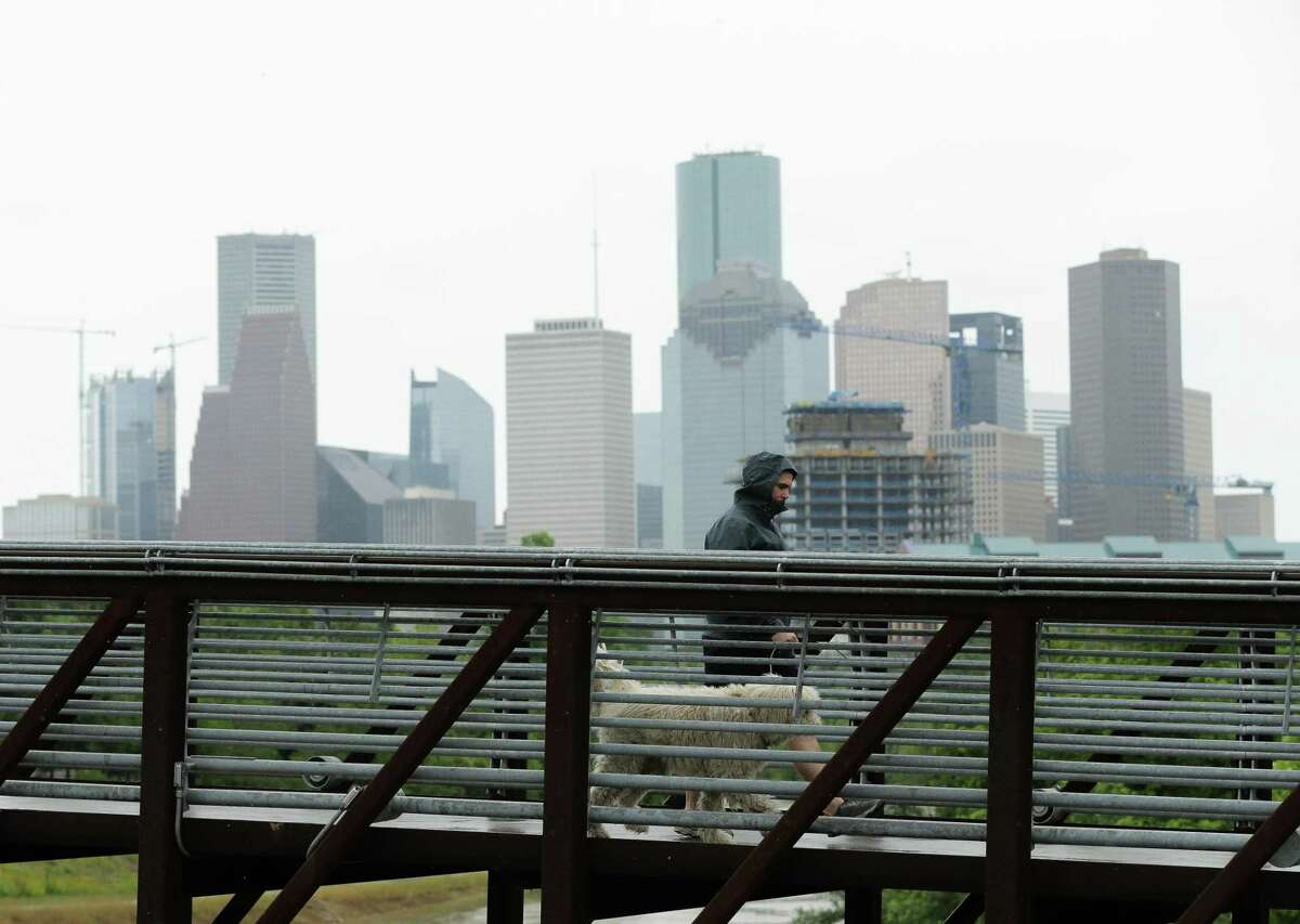 A man and dog cross the Rosemont Pedestrian Bridge as light rain descends on Wednesday, May 19, 2021, in Houston.