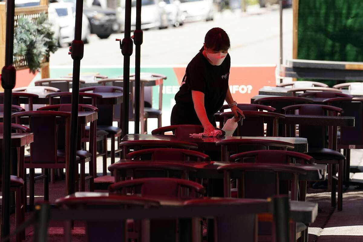 In this May 18, 2021, file photo tables are cleaned in an outdoor eating area in Burbank amid the COVID-19 pandemicCalifornia will mostly rely on the honor system to enforce new masking rules that let vaccinated people forego face coverings in almost all settings starting next Tuesday, when the state fully reopens,.