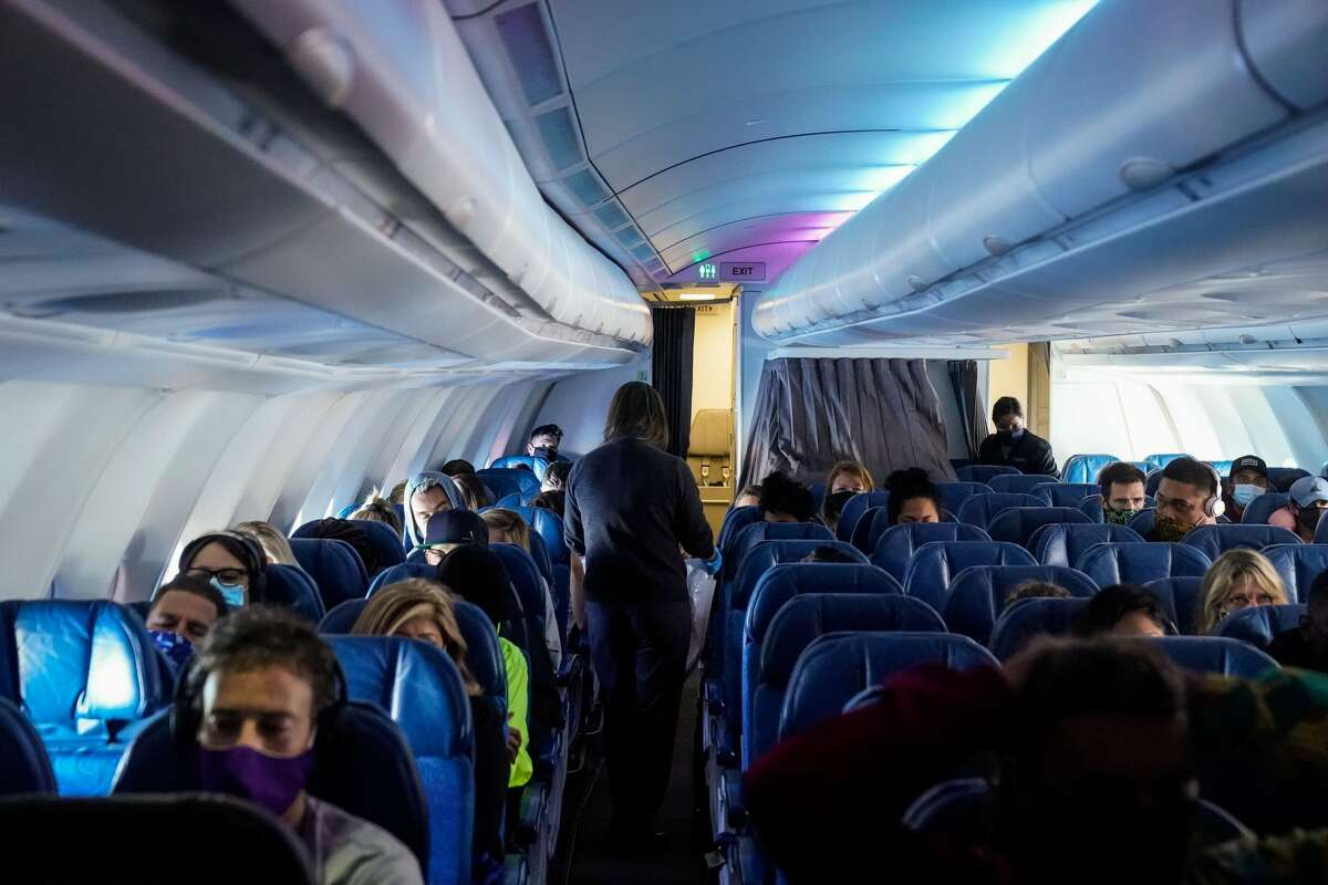 HONOLULU, HI - OCTOBER 15: Masked passengers, aboard a Hawaiian Airlines flight from Los Angeles International Airport to Honolulu International Airport on Thursday, Oct. 15, 2020 above the Pacific Ocean.(Kent Nishimura / Los Angeles Times via Getty Images)
