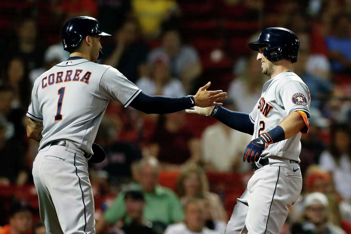 Houston Astros' Alex Bregman (2) celebrates his two-run home run that also drove in Carlos Correa (1) during the eighth inning of a baseball game against the Boston Red Sox, Wednesday, June 9, 2021, in Boston. (AP Photo/Michael Dwyer)