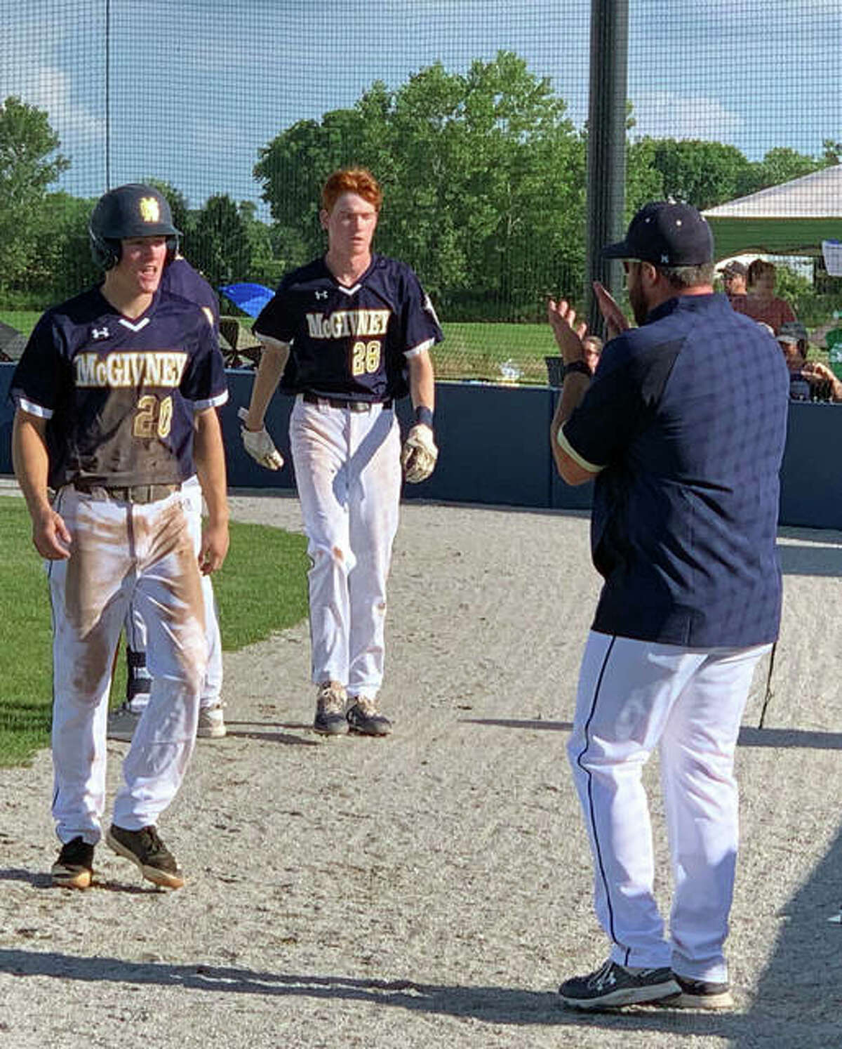 Daniel Gierer, left, and Drew Sowerwine are greeted as they enter the dugout after scoring on a two-run triple by Jackson Rodgers.