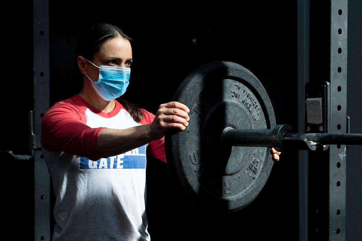 Crossfit Golden Gate gym owner Danielle Rabkin wears a mask while arranging weights before working out at her gym in San Francisco, Calif. Tuesday, October 13, 2020.