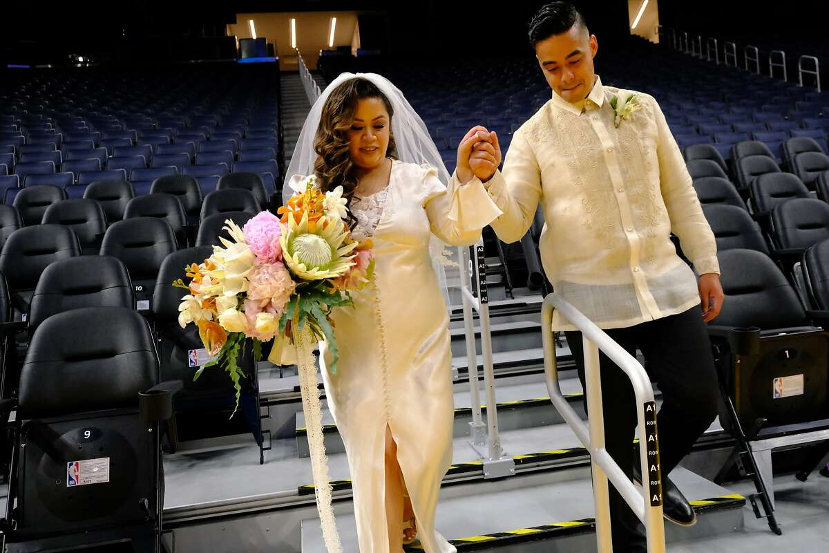 Angelina Marie Yambao and Rowell Fiel walk down to the Chase Center court to take wedding photographs.