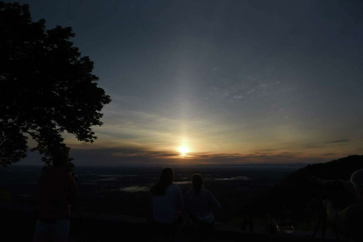 Celestial gazers observe a sunrise solar eclipse from the John Boyd Thacher State Park Overlook on Thursday morning, June 10, 2021, in New Scotland, N.Y. This kind of eclipse has only happened in our area twice in the past 150 years: in 1959 and 1875. (Will Waldron/Times Union)
