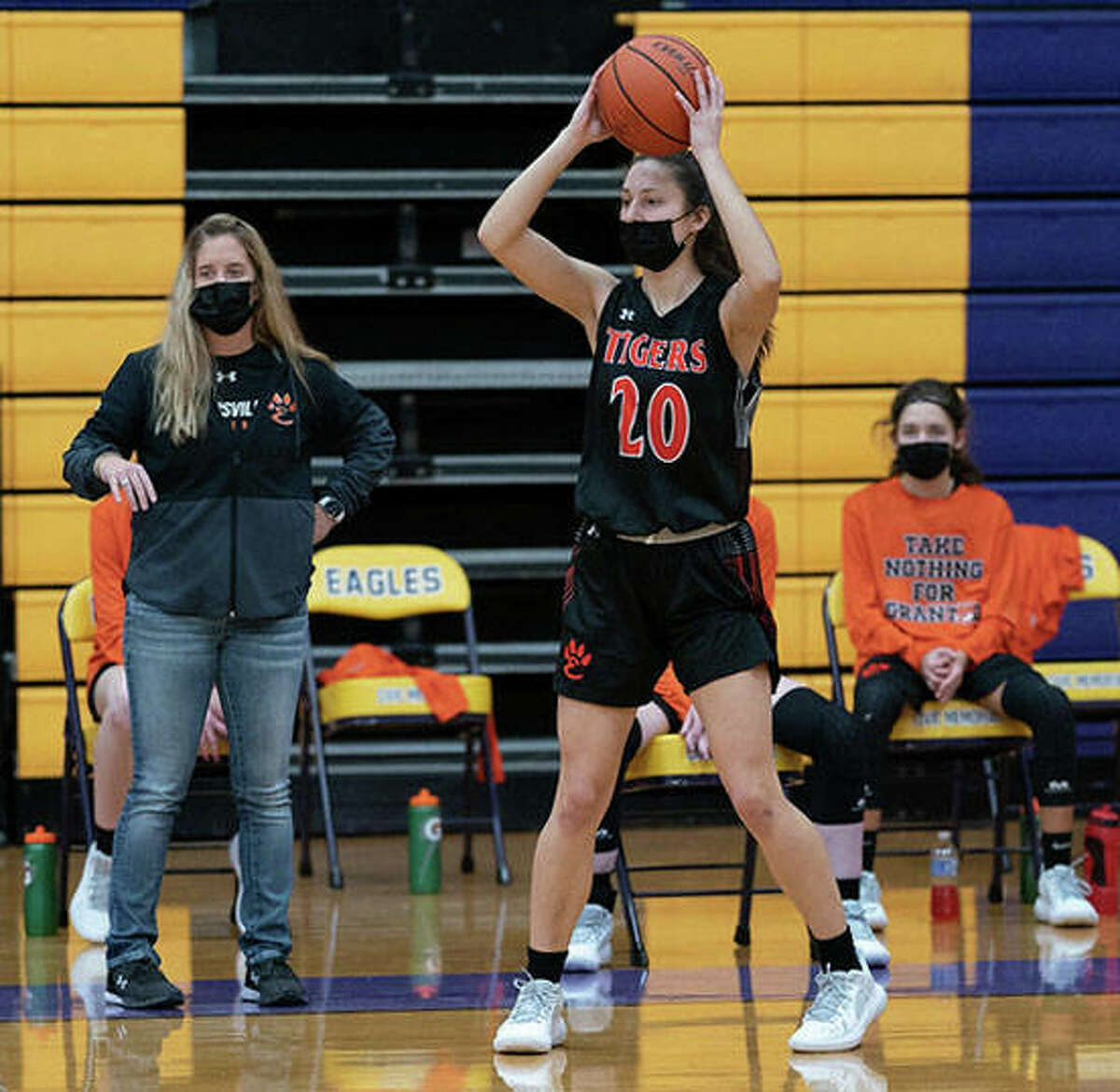 Edwardsville girls basketball coach Caty Happe looks on from the sideline as Emerson Weller looks for an open teammate to pass to during a game at Civic Memorial.