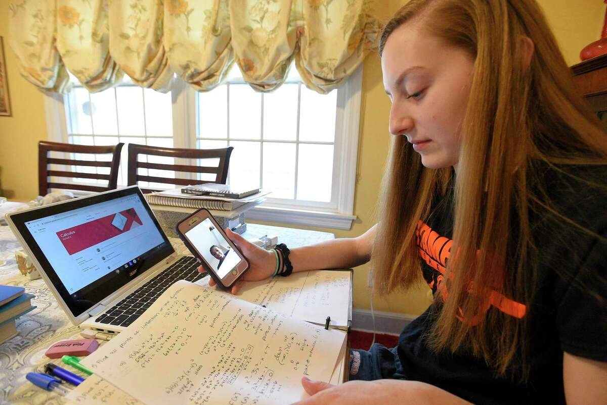 Megan Landsiedel, a senior at Stamford High School, sits with her books at her home in Stamford, Connecticut on March 17, 2020. Landsiedel uses Facetime to connect with Widline Thomas, a fellow classmate, while the two work on a calculus project together, while studying in a virtual learning environment.
