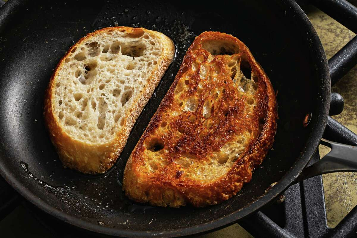Bread being fried in a pan.