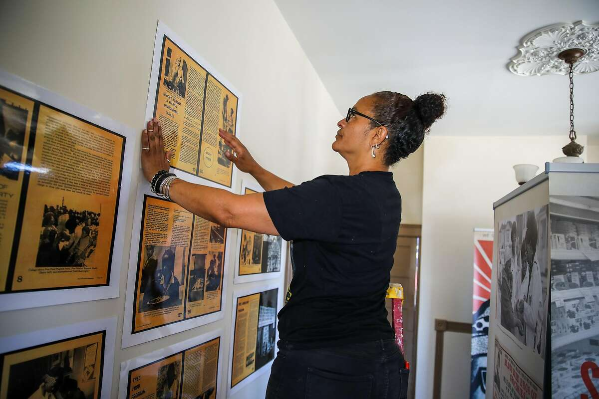 Jilchristina Vest hangs a Black Panther Party image, curated by Lisbet Tellefsen, an Oakland-based archivist, publisher, curator, and collector, inside her home on Wednesday, June 9, 2021, in Oakland, Calif.