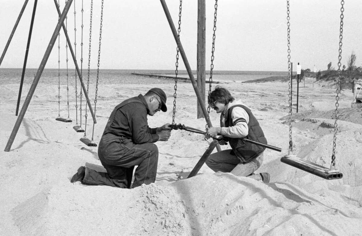 Manistee City employees Al Schmeling (right) and Warren Klemeks repair and put up playground equipment at First Street Beach today. The pair started working on the project yesterday in preparation for the summer season. The photo was published in the News Advocate on June 11, 1981. (Manistee County Historical Museum photo)