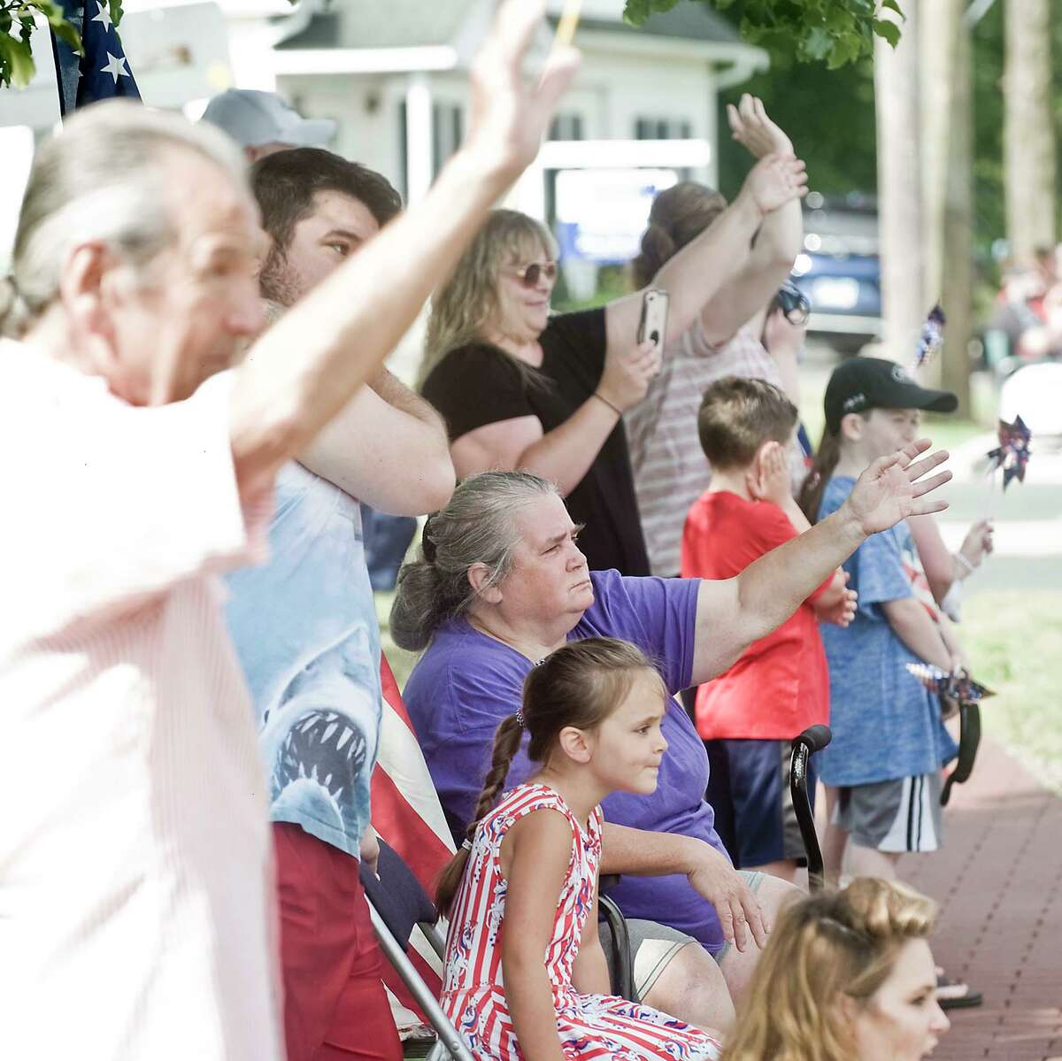 Spectators wave at last year's Fourth of July car parade in New Fairfield, Conn.