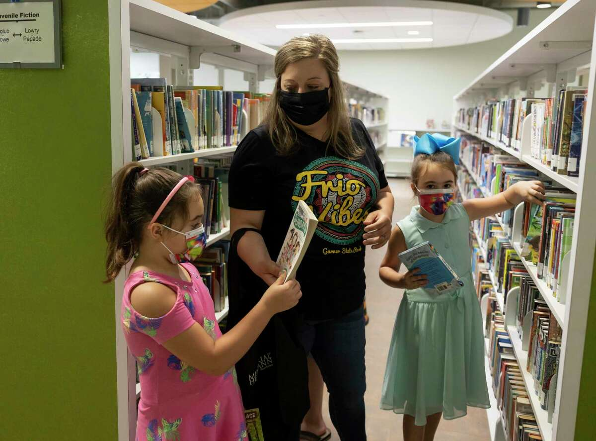 Leslie, center, assists her 7-year-old twin daughters, Evelynn, right and Sophia, as they look through books at the Kingwood library, Wednesday, June 9, 2021, in Kingwood. Libraries through the Harris County Public Library system were closed due to the COVID-19 pandemic but recently opened again at 75% of buildings' maximum capacity after the county upgraded the COVID-19 threat level.