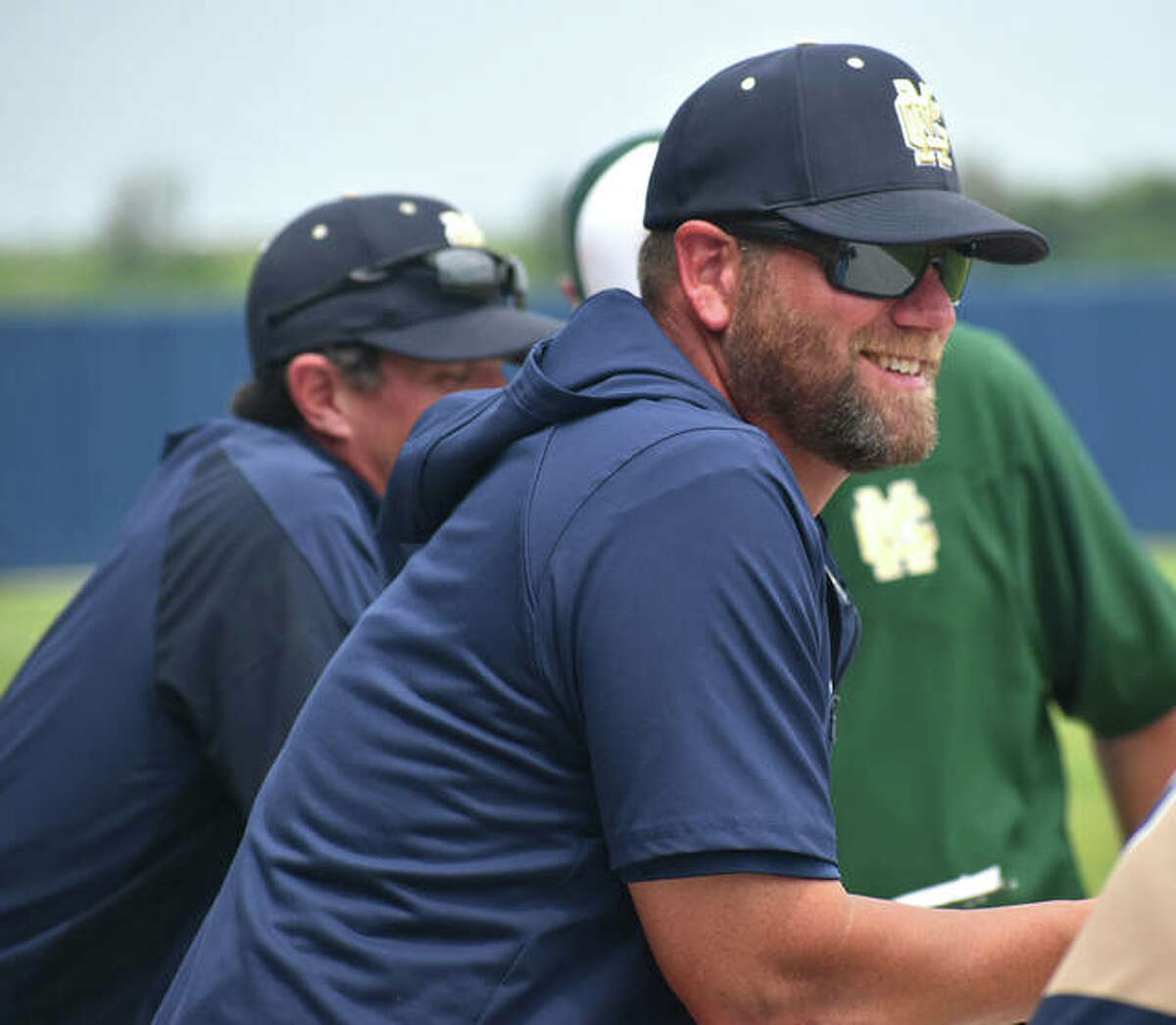 Father McGivney coach Chris Erwin watches from the dugout during a game against Collinsville in the regular season.