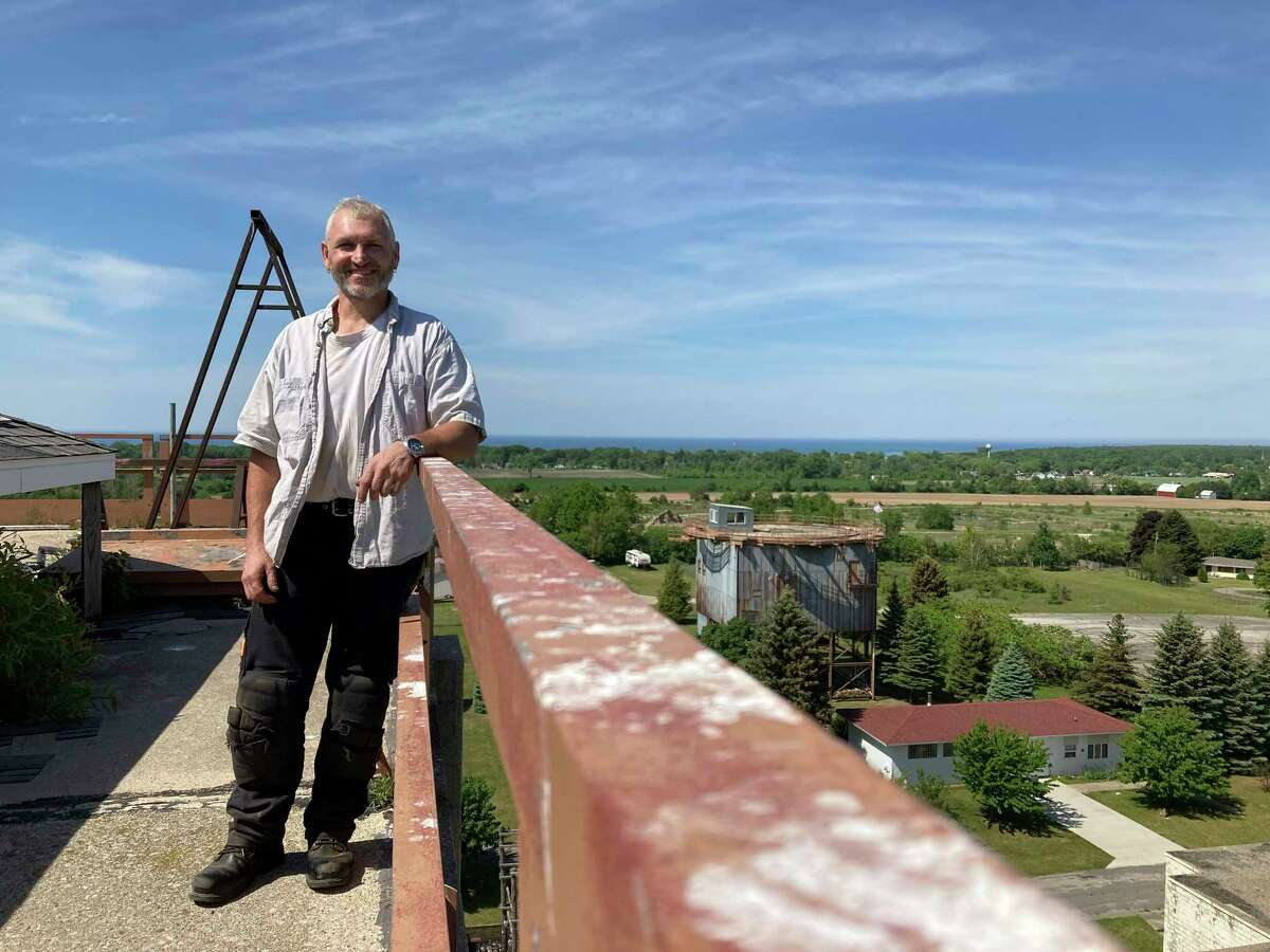 David Gilbert poses on the roof of the abandoned military tower, which overlooks Port Austin, on June 4. (Teresa Homsi/Huron Daily Tribune)