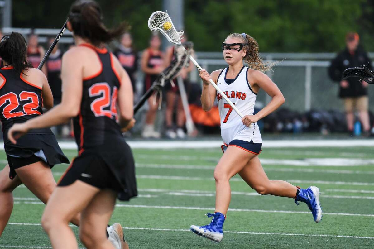 Midland's Delaney Abbott brings the ball up field during a state semifinal game against Rockford Wednesday, June 9, 2021 at Haslett High School. (Adam Ferman/for the Daily News)
