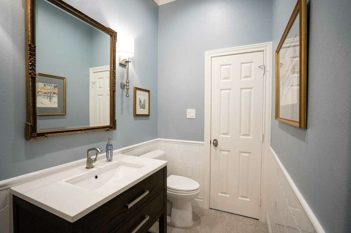 After: A full bathroom attached to the home office got an updated cabinet and pretty tile.