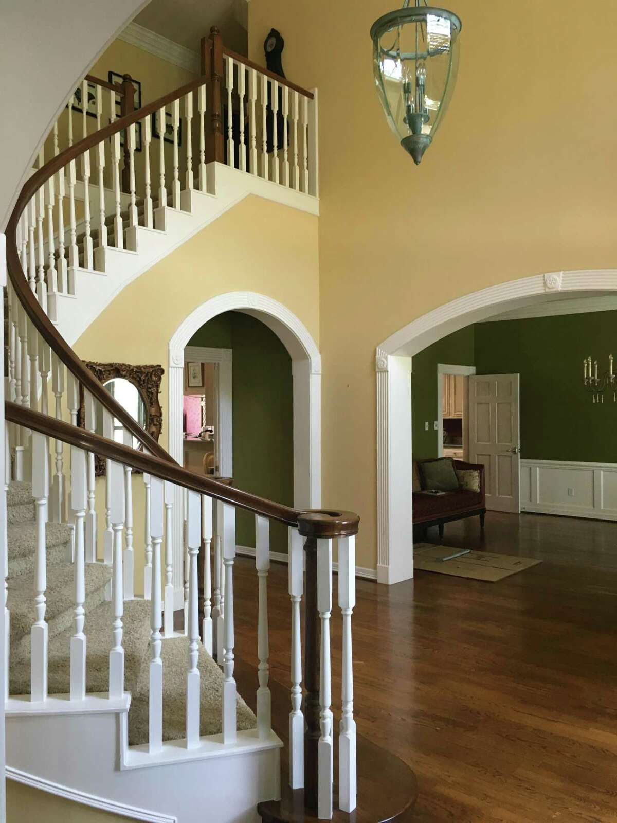 Before: Traditional wood spindles lined the staircase, and darker wood planks covered the foyer, dining room and game room.