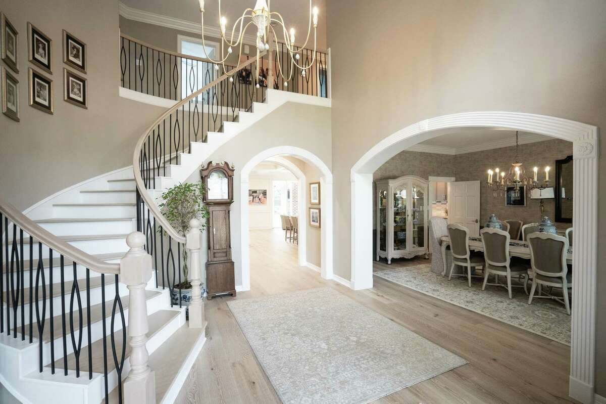 After: The foyer's update includes a wrought iron and wood banister and European white oak floors that spread through most of the main floor.