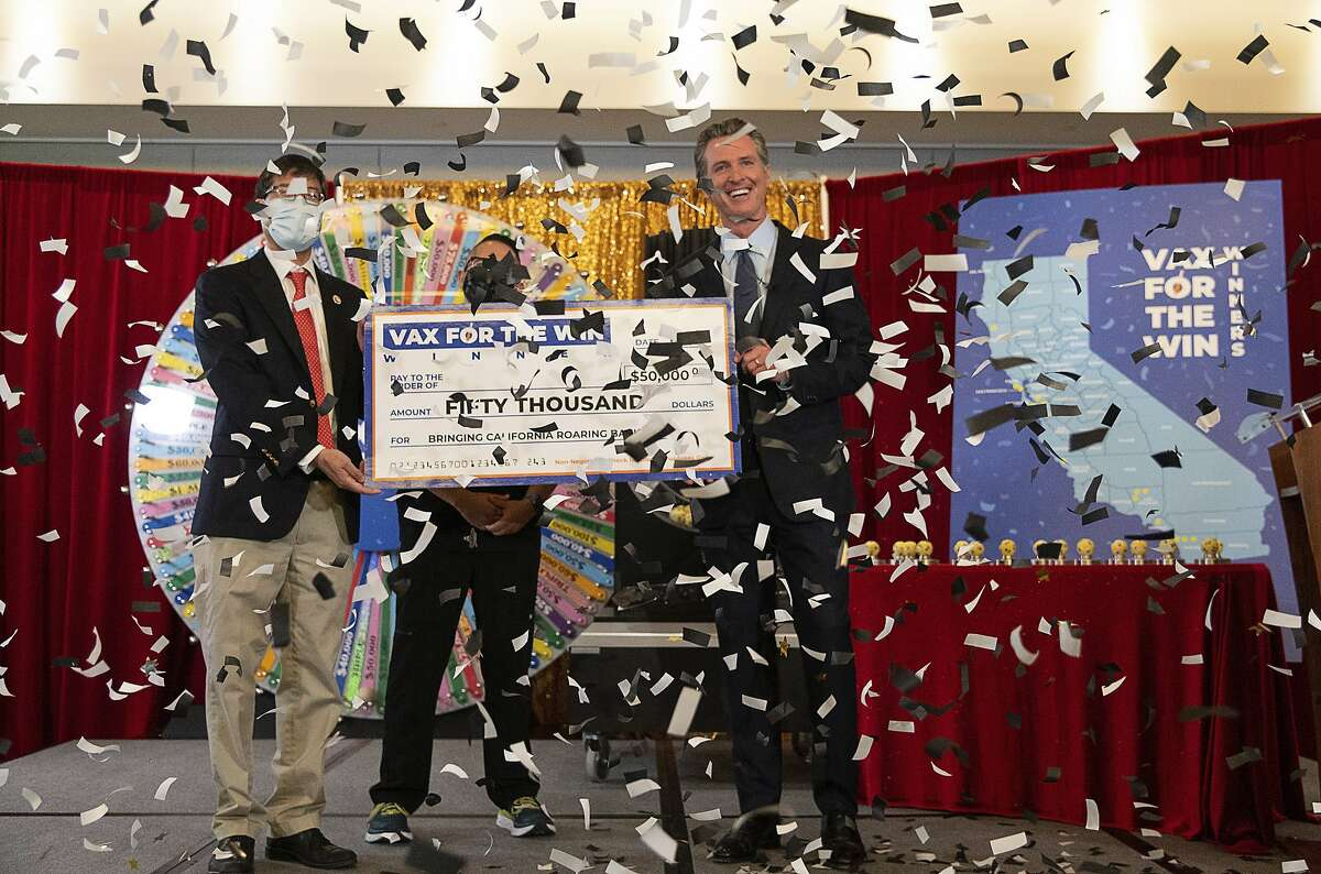 Gov. Gavin Newsom, state Sen. Richard Pan, left, and UC Davis assistant nurse manager Claudio Alvarado, center, hold a mock check as the state drew the first 15 winners to be awarded $50,000 for getting vaccinated against COVID-19 at the California Lottery on Friday in Sacramento.