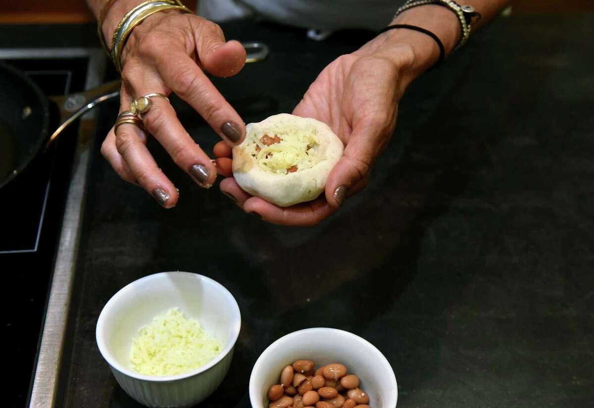 Caroline Barrett makes cheese-and-bean pupusasat Different Drummer's Kitchen in Guilderland. (Will Waldron/Times Union)