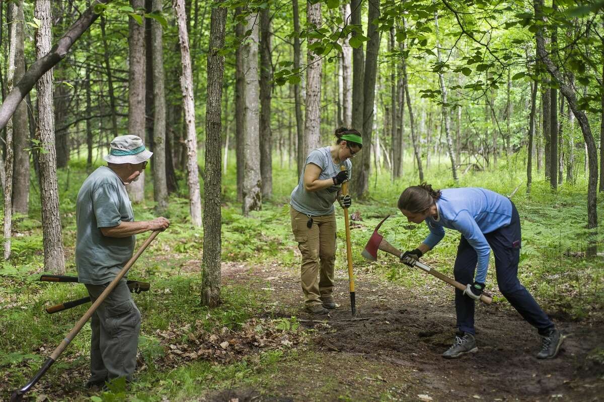 Volunteer Denny Brooks, left, Little Forks Conservancy preserve and volunteer manager Sara Huetteman, center, and AmeriCorps member Kaitlynn Burkhard, right, work to smooth a patch of trail Tuesday, June 8, 2021 at the Riverview Natural Area in Midland as part of LFC's weekly