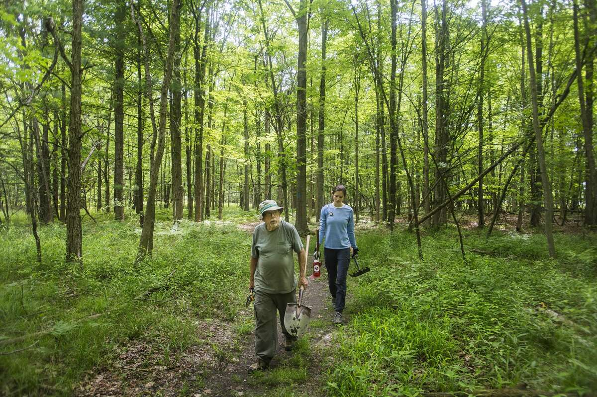 Volunteer Denny Brooks, left, and AmeriCorps member Kaitlynn Burkhard, right, walk along a trail looking for areas needing improvement Tuesday, June 8, 2021 at the Riverview Natural Area in Midland as part of Little Forks Conservancy's weekly