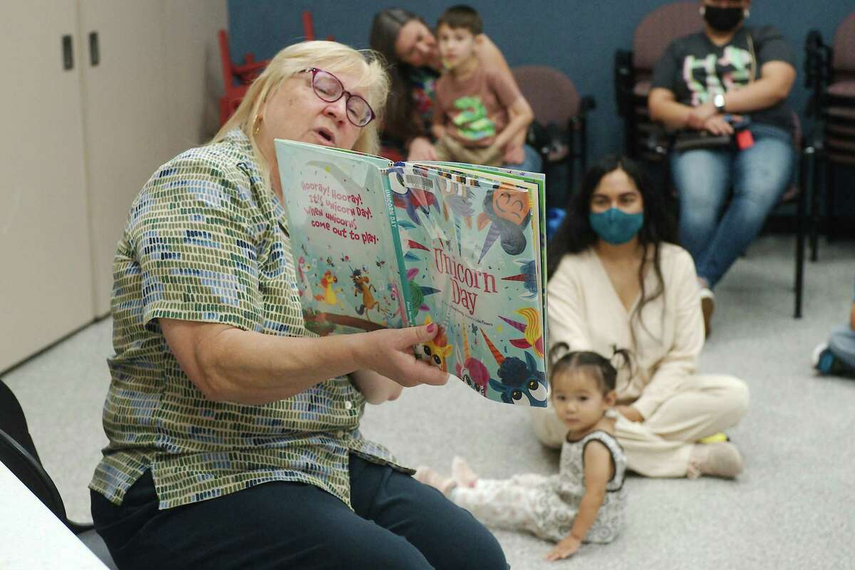 Fairmont Library Children's Librarian Leslie Guhl reads a story during family story time to Nancy Zamrron and her son, Ian and to Lissette Lam with her daughter, Miette.