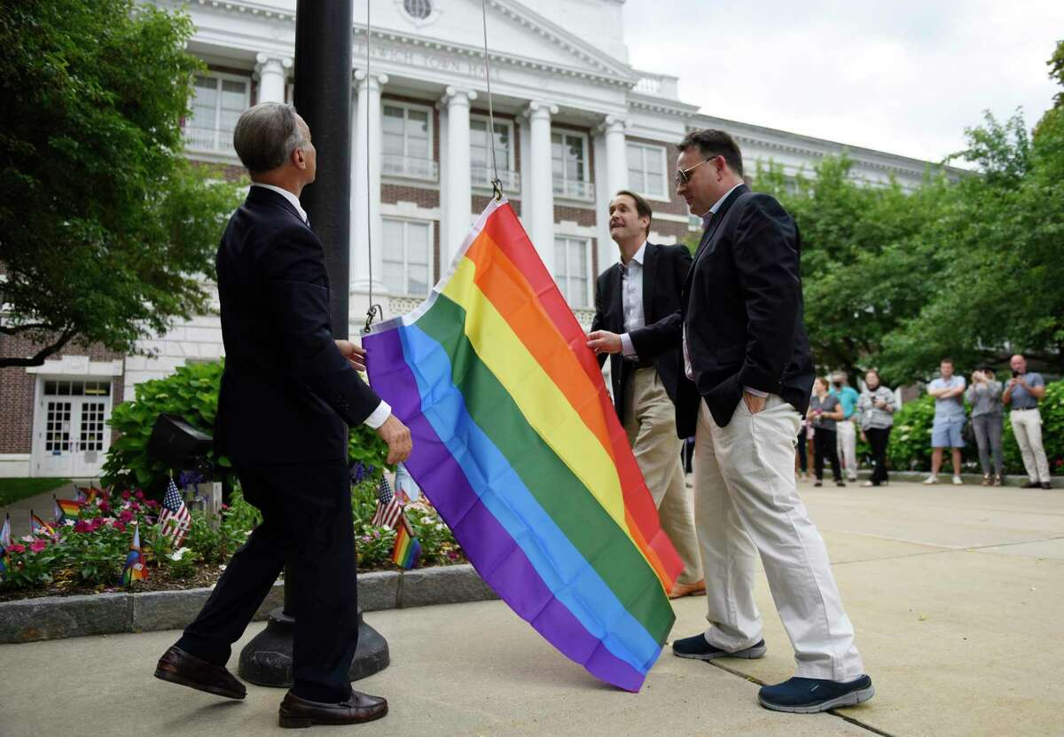 First Selectman Fred Camillo, left, U.S. Rep. Jim Himes, D-Conn., center, and former Selectman Drew Marzullo raise a rainbow flag during the Pride Month LGBTQ+ ceremony at Town Hall in Greenwich, Conn. Thursday, June 10, 2021. Former Selectman Drew Marzullo, the town's only openly-gay Selectman, joined First Selectman Fred Camillo and U.S. Rep. Jim Himes, D-Conn., to acknowledge the progress that has been made in acceptance of the LGBTQ+ community while noting that there is still much work to be done.