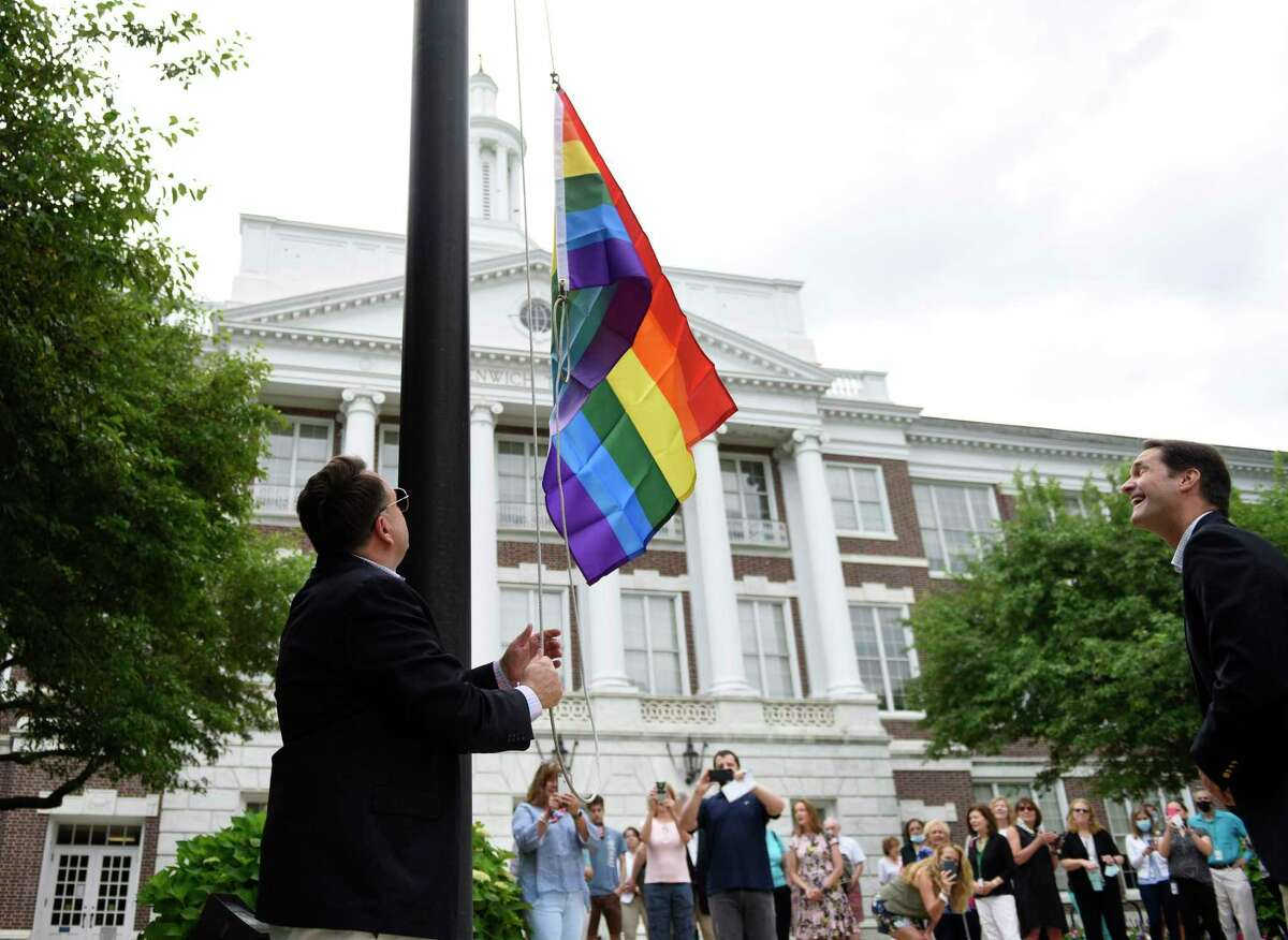 Former Selectman Drew Marzullo raises a rainbow flag during the Pride Month LGBTQ+ ceremony at Town Hall in Greenwich, Conn. Thursday, June 10, 2021. Former Selectman Drew Marzullo, the town's only openly-gay Selectman, joined First Selectman Fred Camillo and U.S. Rep. Jim Himes, D-Conn., to acknowledge the progress that has been made in acceptance of the LGBTQ+ community while noting that there is still much work to be done.