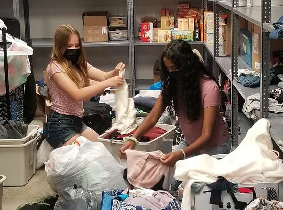Caroline James, left, and Veda Kommineni sort through donations in Veda's Care Closet, which came about from the girls bringing snacks in their backpacks to school for peers who weren't eating lunch. Their project grew from backpacks to Care Lockers to adding a Care Closet at Liberty Middle School.