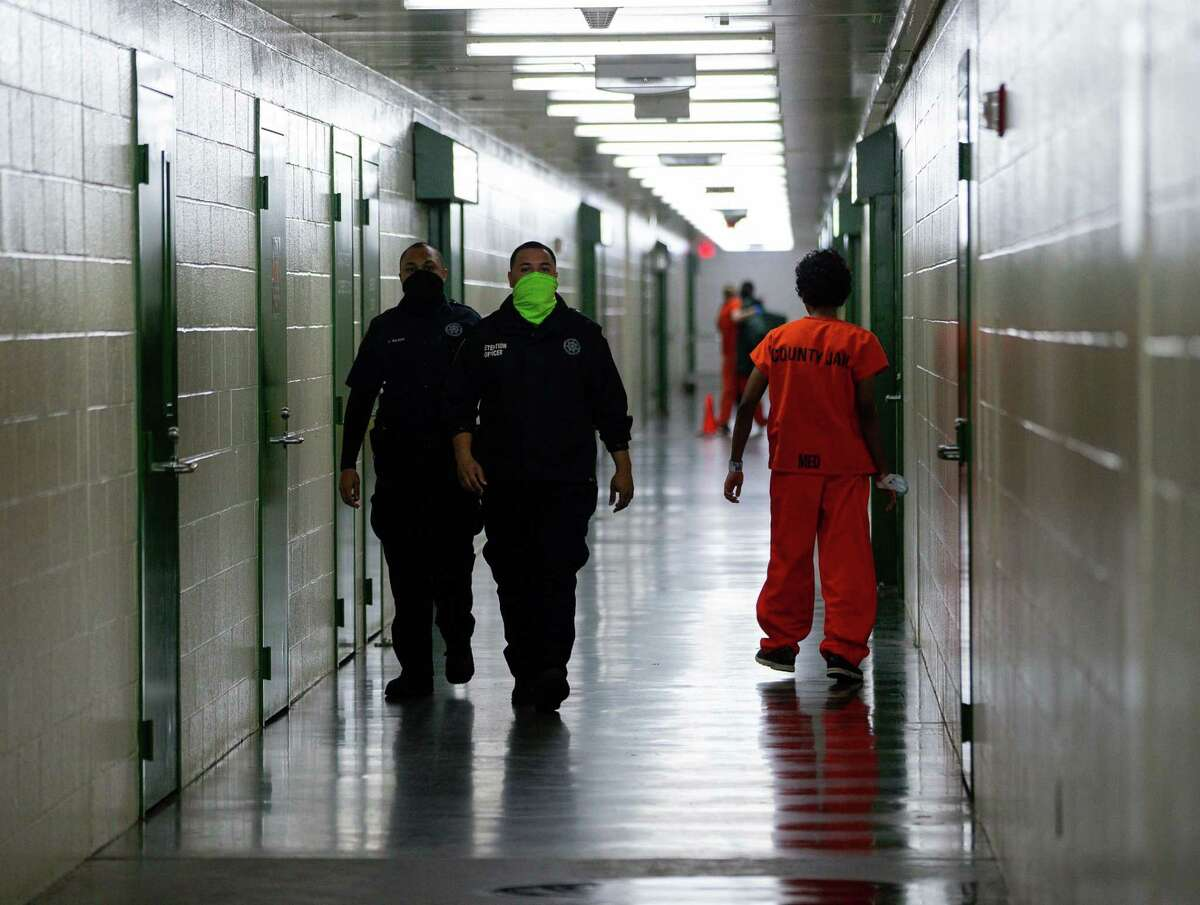 Harris County Sheriff's Office deputies walk past an inmate inside the Harris County Jail on Thursday, Jan. 14, 2021, in Houston.