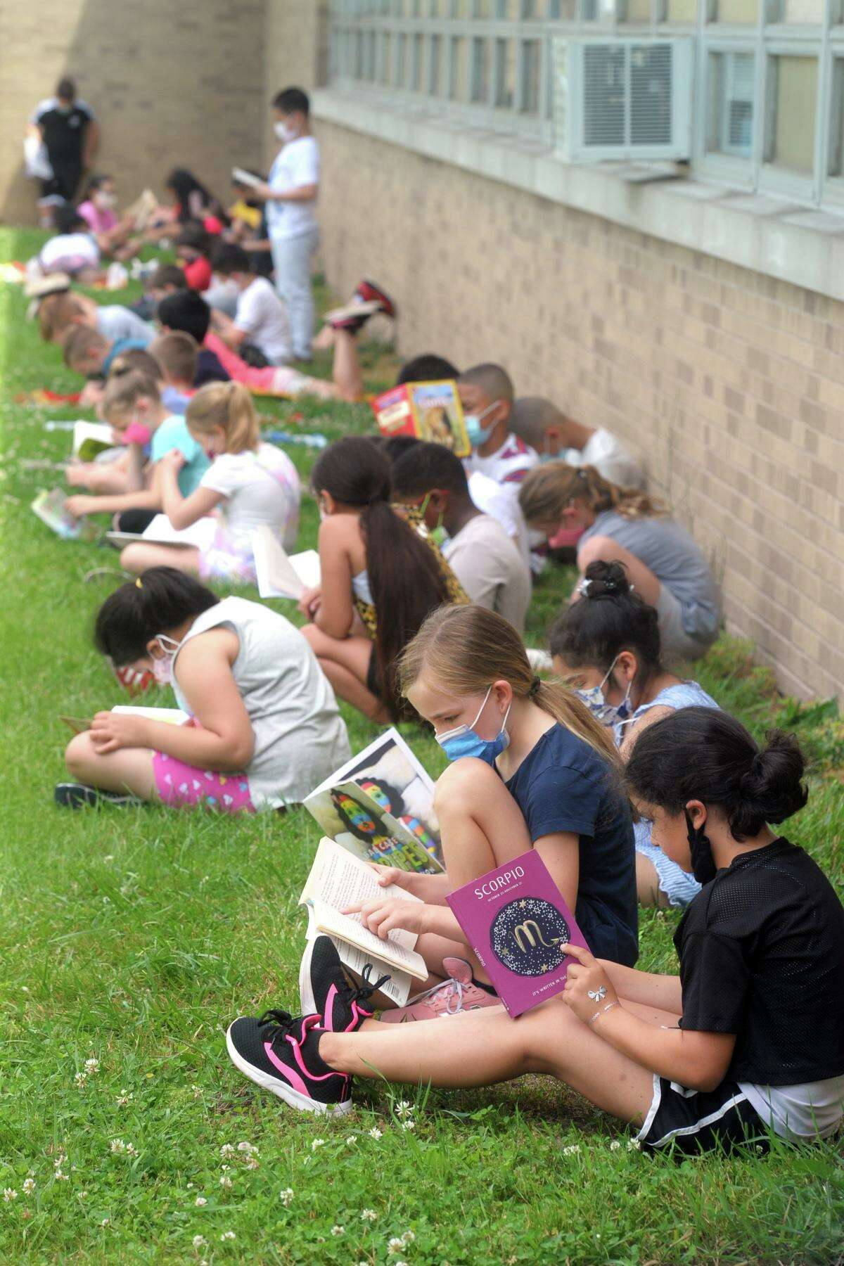Students read in the shade of their school building on a sweltering morning as they take part in the kickoff event for the summer reading program at Long Hill School, in Shelton, Conn. June 8, 2021.