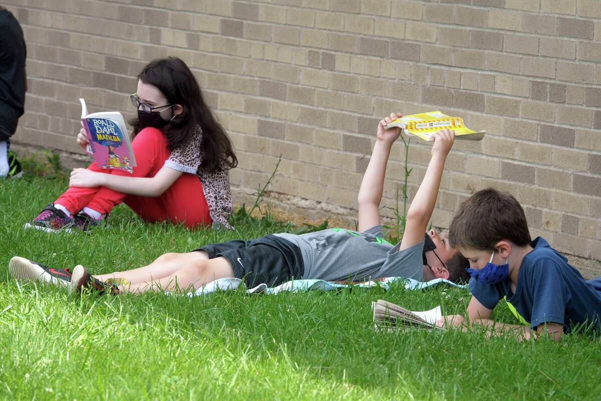 Students read in the shade Long Hill School in Shelton on Tuesday.