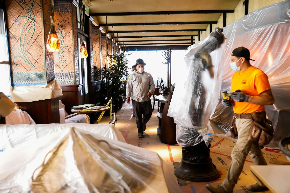 Workers walk through Boulevard restaurant while doing renovations to install new fabric designs and repaint before their reopening later this summer on Friday, May 28, 2021 in San Francisco, California.