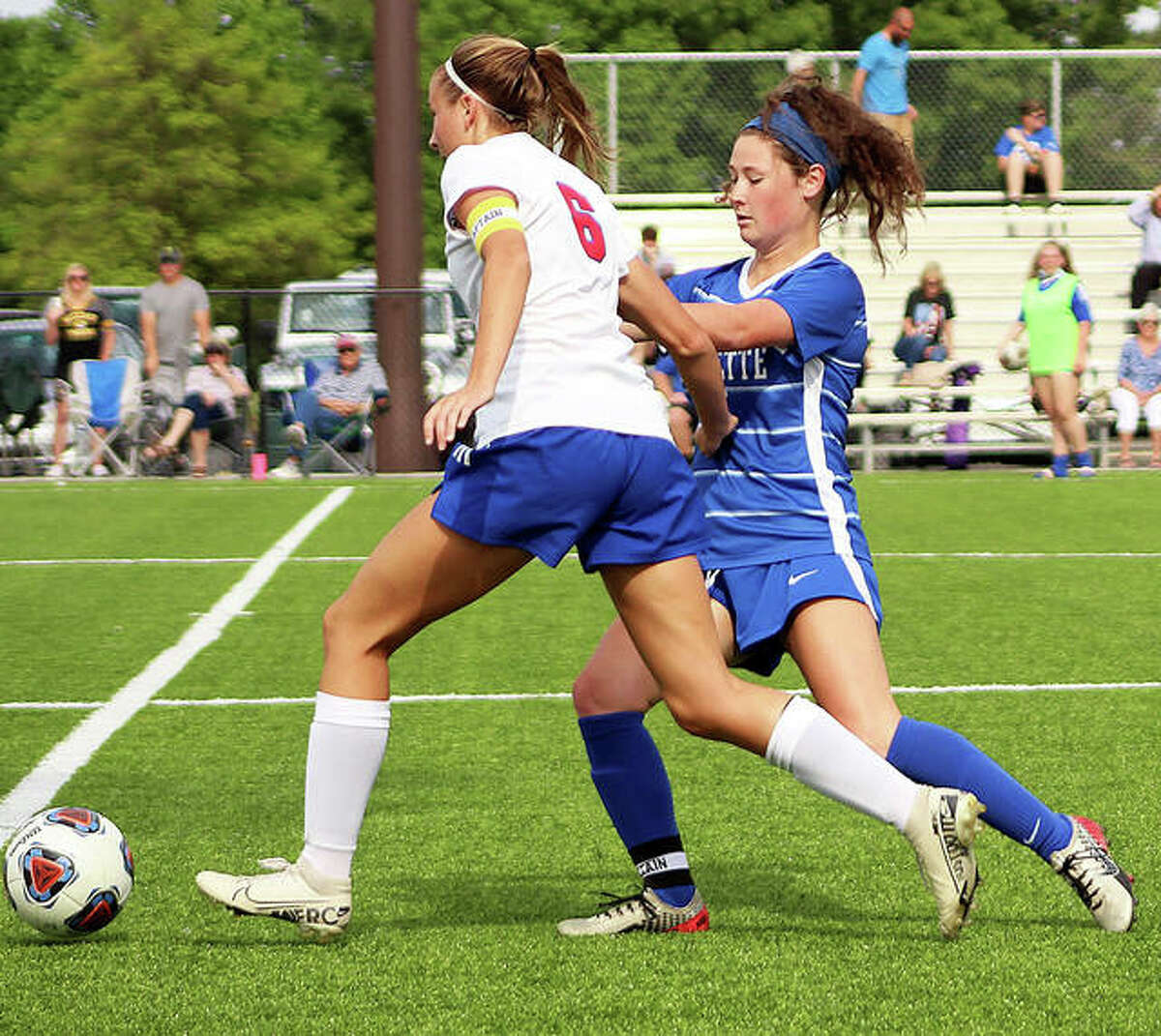 Macie Lucas of Roxana (6) tries to get around Marquette's Madelyn Smith Friday during a May 21 game at Gordon Moore Park. The teams will play a rematch Friday for a Class 1A sectional championship at 4:30 at the Wood River Soccer Park.
