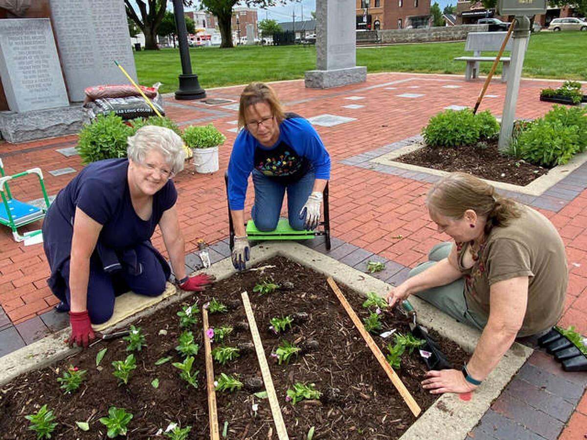 Edwardsville Garden Club members, left to right, Linna Joseph, Lori Klenke and Denise Saska plant rows at the Blue Star Memorial Garden in Edwardsville City Park.