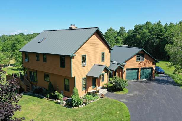 """This week's house has a castle vibe in the Fulton County countryside. Built in 2003, 162 Hatzenbuhler Road, Broadalbin has a routine front entrance but the back says """"party,"""" with a turret, a porch, balcony and hot tub at ground level. The house has 3,800 furnished square feet and sits on 49 acres where there are streams and a pond. The Great Sacandaga Lake is 1.5 miles away. The interior style is rustic with granite counters and a stone fireplace. Oil fuels a radiant heating system with seven zones, including the garage. There are three bedrooms and three bathrooms. The three-car garage is attached by a covered walkway. A metal barn on the property contains a 600-square-foot apartment; there's also pole barn on the lot. Broadalbin-Perth schools. Taxes: $12,502. List price: $731,000. Contact listing agent Scott Varley of Keller Williams Capital District at 518-281-6808."""