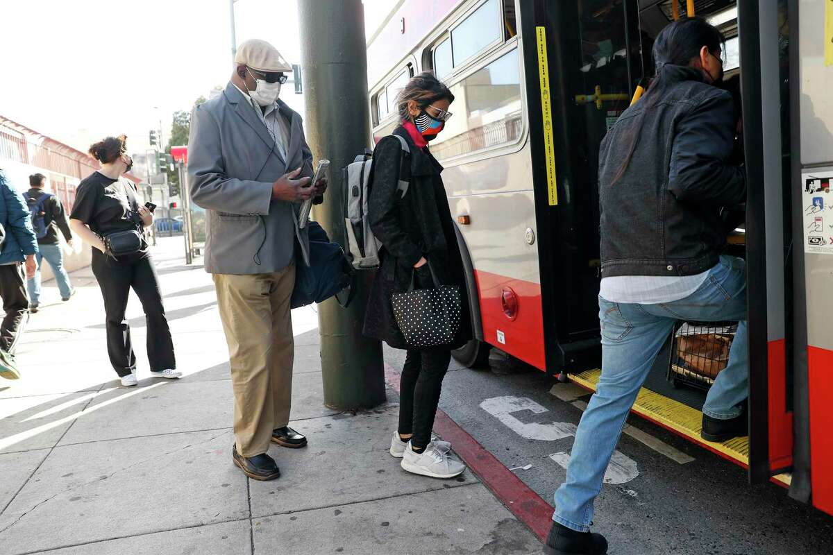 Asy Dhaif (center) boards the Muni 14 Mission bus on Mission Street at 8th Street in San Francisco, Calif., on Monday, April 19, 2021. Muni implemented one of its first emergency transit-only lanes that the agency says has helped improved bus travel times during the pandemic. Muni is planning on making some of these transit-only lanes permanent.