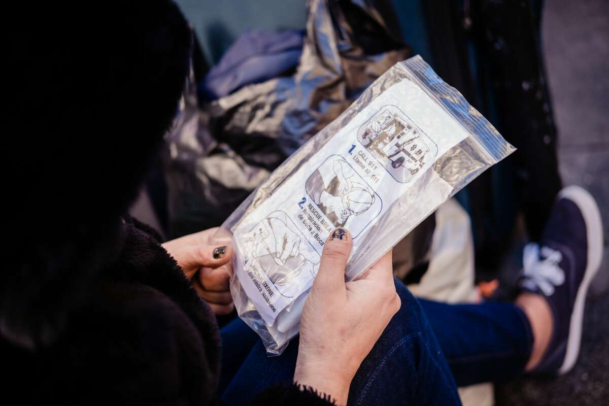 In this file photo, a drug user looks at the package of Narcan she was handed by Paul Harkin, director of harm reduction at GLIDE, who was walking the streets to handout Narcan, fentanyl detection packets and tinfoil to those drug users in need as a part of outreach on the streets of San Francisco on Feb. 3, 2020.