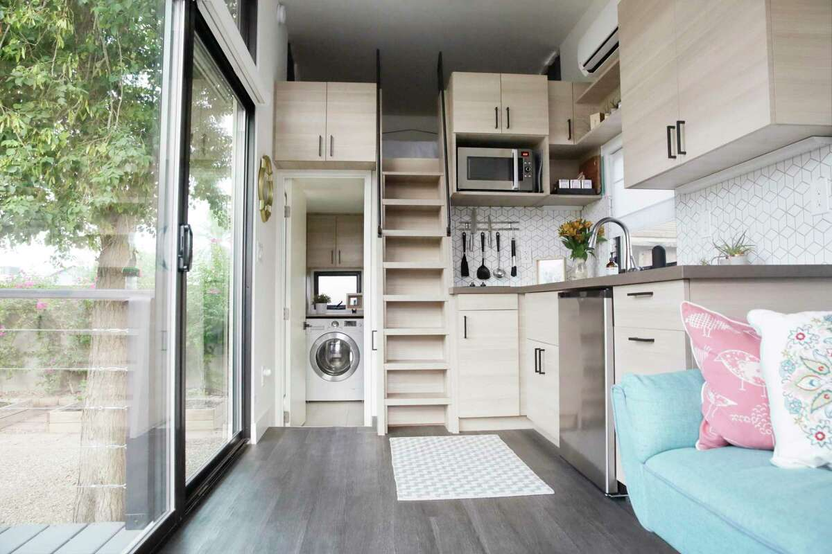 The interior of a tiny house with large glass windows, showcase the kitchen, part of the living room and loft bedroom.