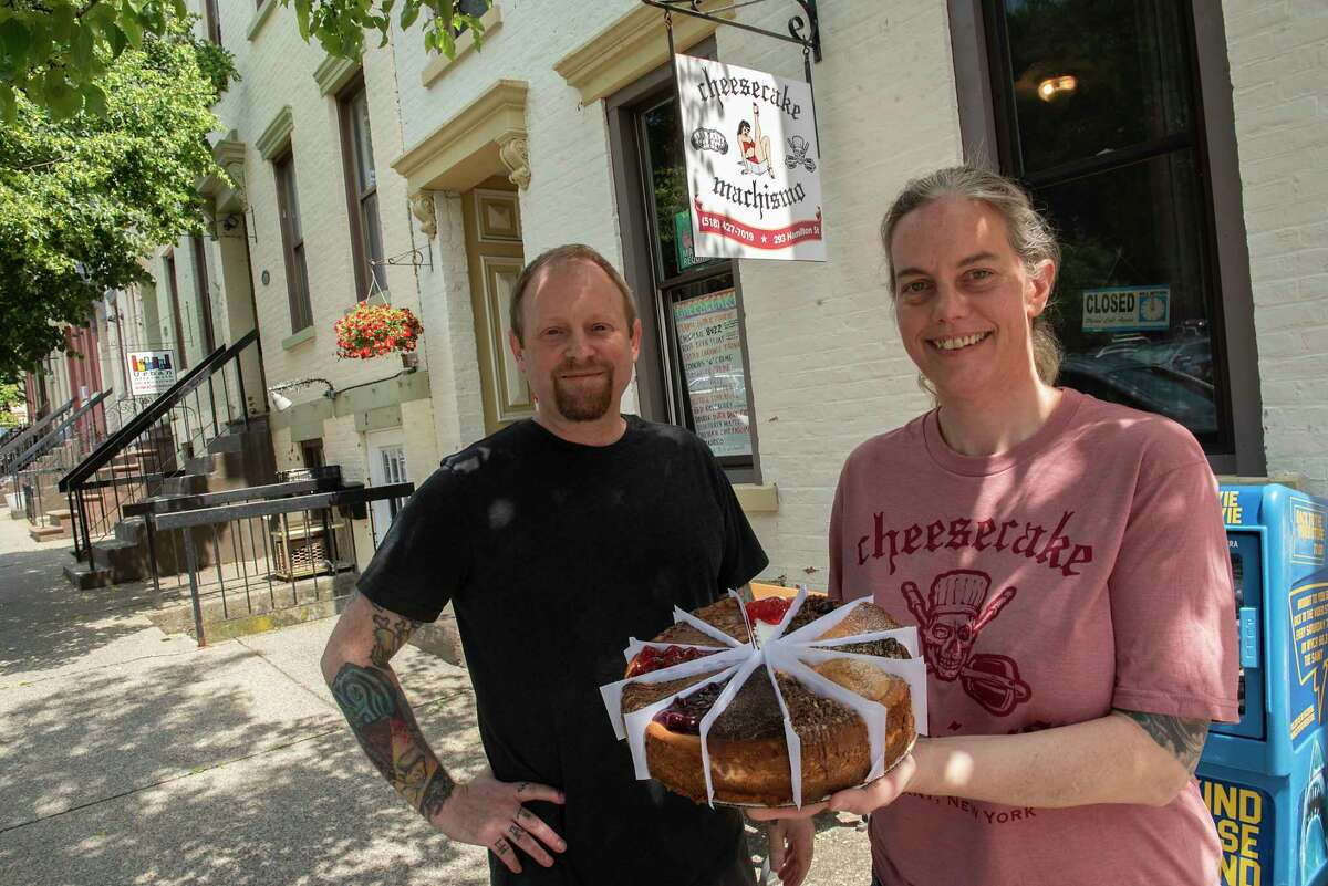 Co-owners Bam Lynch, left, and Lynn Beaumont show off a 'frankencake' in front of their store Cheesecake Machismo in Albany. A frankencake is a 12-slice cheesecake made from a variety of flavors. (Lori Van Buren/Times Union)