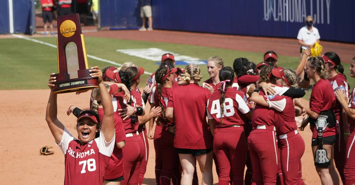 Oklahoma's Jocelyn Alo (78) carries the championship trophy toward the Oklahoma fans as the team celebrates after defeating Florida State in the final game of the NCAA Women's College World Series softball championship series Thursday, June 10, 2021, in Oklahoma City. (AP Photo/Sue Ogrocki)