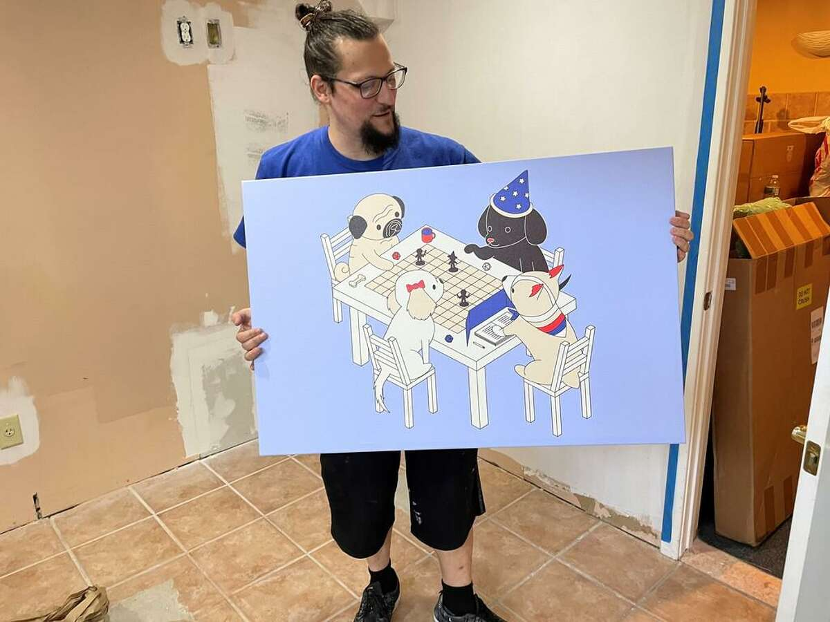 At Unison Games Cafe, co-owner David Letourneau shows off art he plans to use to decorate the store.