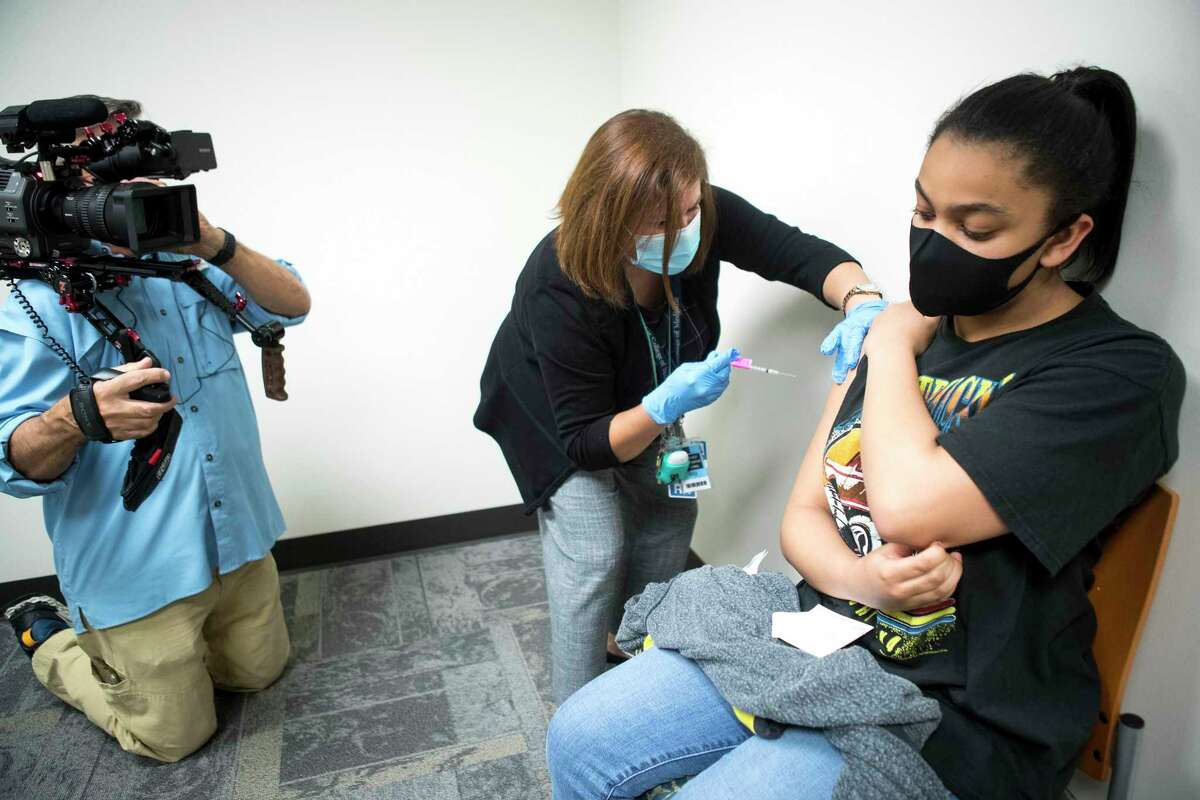 Kennedy Gant, 12, receives a dose of the Pfizer BioNTech COVID-19 vaccine from registered nurse Lisa Icard at Baylor College of Medicine Wednesday, May 12, 2021 in Houston. Gant was in the group of first teenagers to receive the COVID-19 vaccine in the Houston area, less than two hours after federal health officials officially recommended the distribution of the vaccine to 12- to 15-year-olds nationwide.