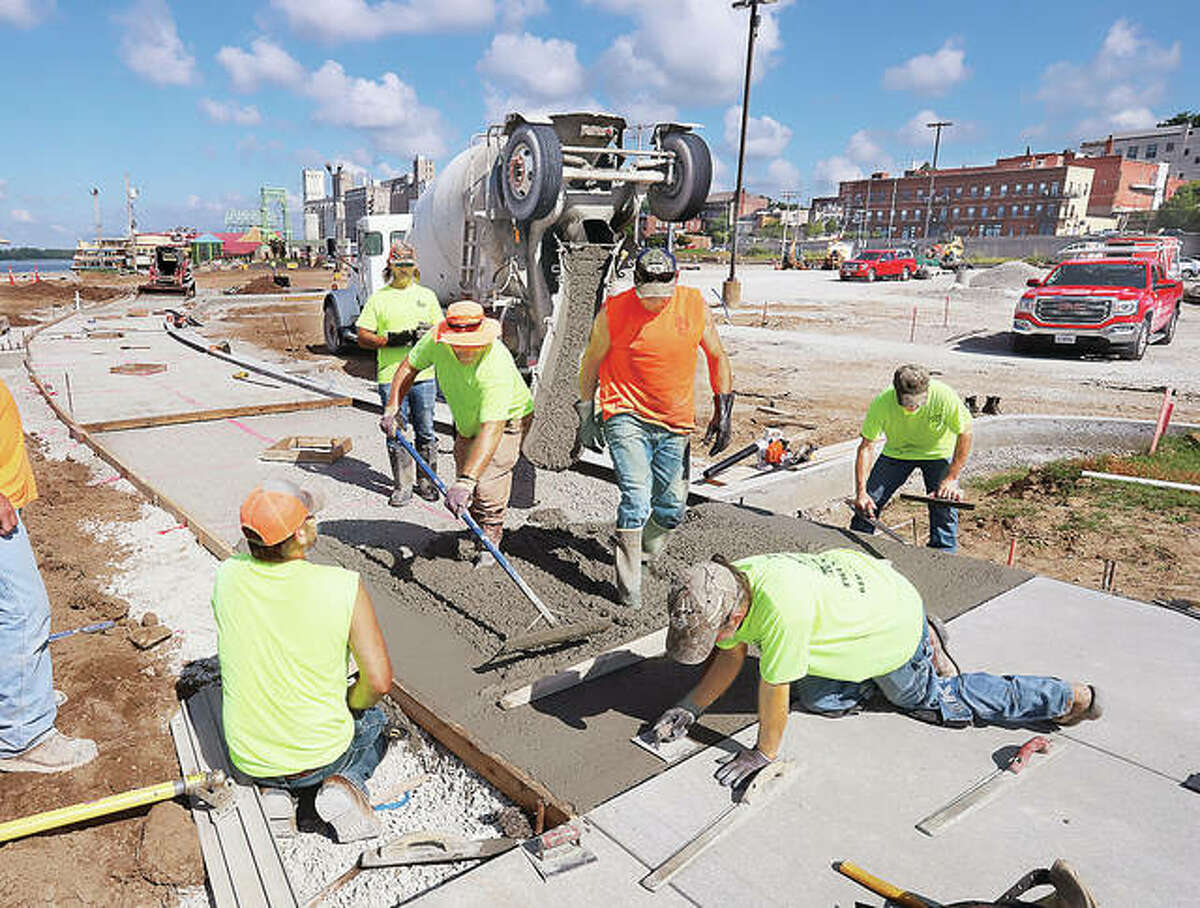 RCS Construction employees were pouring more concrete sidewalks in Alton's Riverfront Park Thursday where work continues on a major renovation project. A separate construction project to build a splash pad and restrooms is also underway nearby.