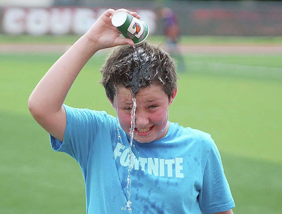 Leo Scarborough dumps water on his head to cool off Thursday morning at the Cougars Soccer Camp.