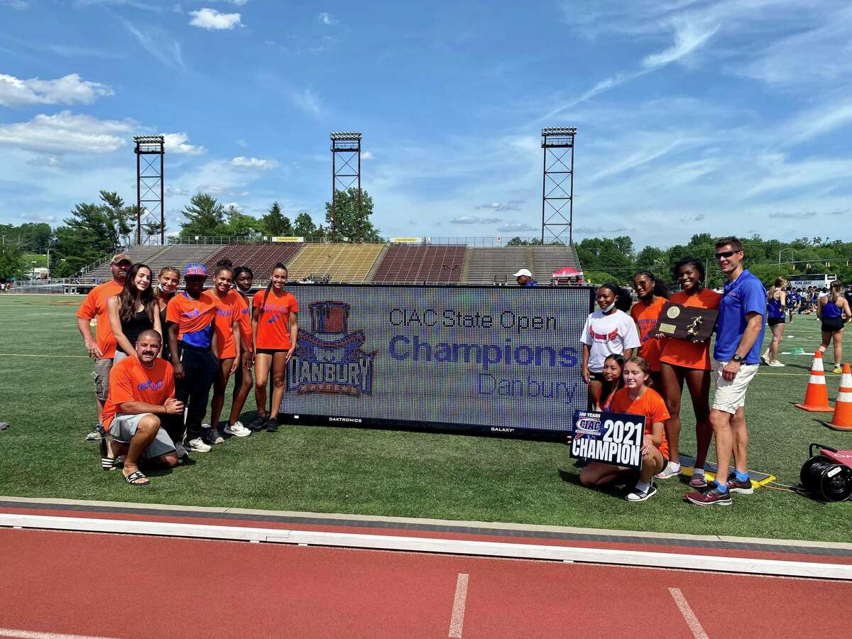 Danbury celebrates winning Girls Track and Field State Open championship on Thursday at Willow Brook Park in New Britain.