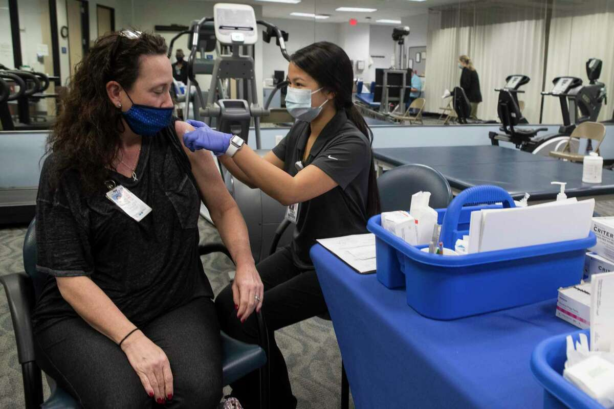 United Airlines employee Stephanie Green, left, receives a Pfizer-BioNTech COVID-19 vaccine in April. The vast majority of Houston employers want their workers vaccinated, but few are requiring it, according to a new survey.